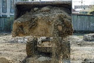Image description: Skid loader with a Virnig bucket hauling dirt.
