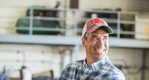 Man in his mid 40s wearing a plaid shirt and trucker hat about the replace a compact tractor cylinder