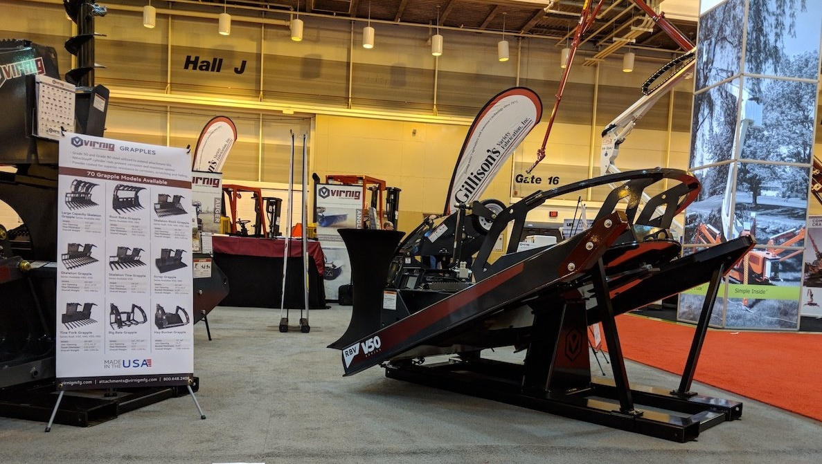 Image description: Virnig's trade show booth setup featuring a brush cutter skid steer attachment in the foreground.