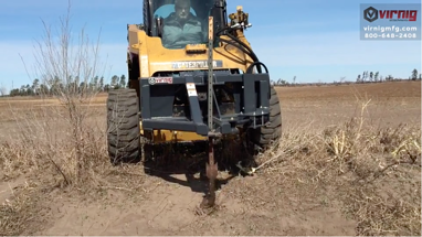 Virnig Tree Puller skid loader attachment pulling a metal post from the ground.